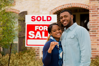 Young couple in front of for sale sign