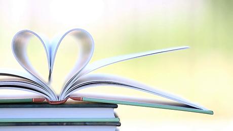 stack-of-open-book-in-wind-green-garden-