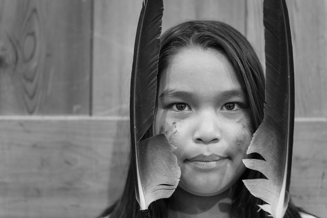 An Indigenous child in Canada peers through two feathers.
