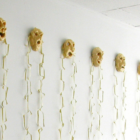 """11 Masks, ceramic, """"hair"""" made out of dyed and cut up book pages"""