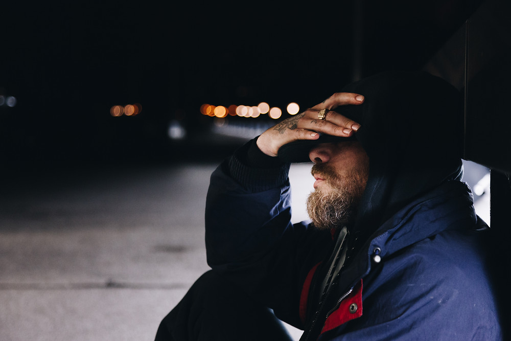 A man holds his forehead, demonstrating stress about income and housing.
