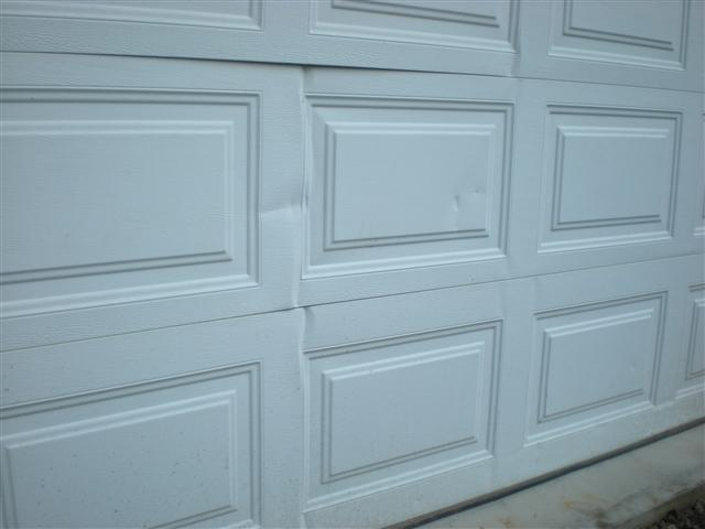Hail damage to a garage door.
