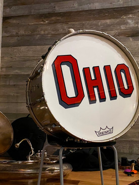Large base drum with red text spelling OHIO and sousaphone laying on floor inn background.