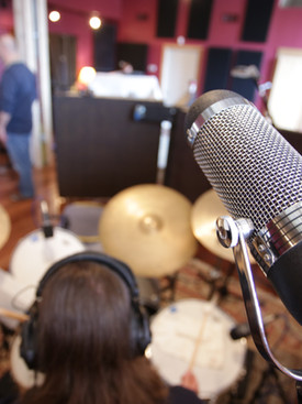 Close up image of microphone over drum set in well light recording studio
