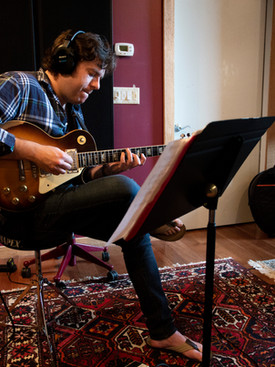 Man sitting in front of music stand playing on vintage guitar in music studio room.