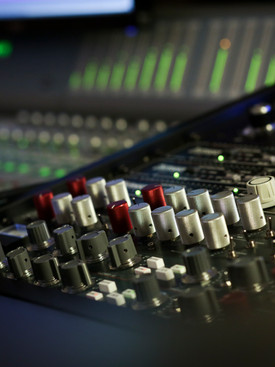 Close up of studio control console board with knobs and dials.