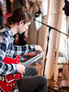 Man with red bass tuning strings while seated in studio