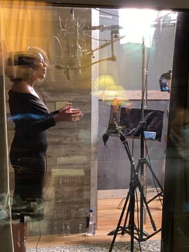 Woman in black singing into microphone in studio