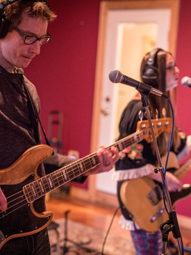 Man holding guitar playing with headphones on next to woman singing into microphone while playing a base in a red recording room.