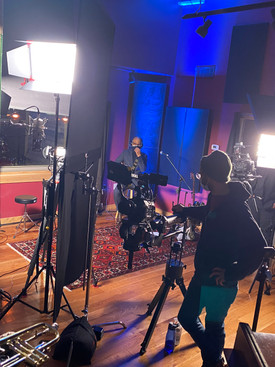 Musicians in recording studio as man stands behind camera and near studio lights recording the music.