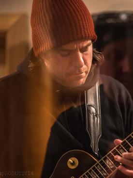 Man in red beanie playing a dark brown guitar in music studio