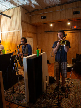 Three men standing near each other in recording studio playing band instruments.
