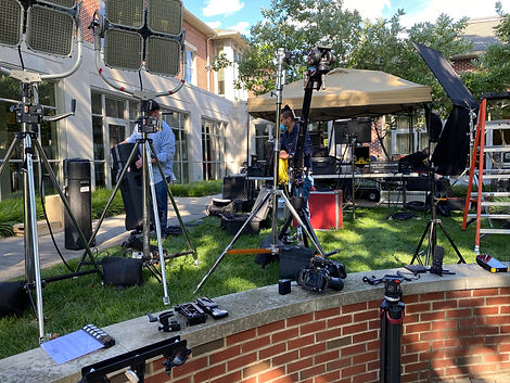 Video production scene outside with cameras, light stands and equipment as people set up equipment for video shoot