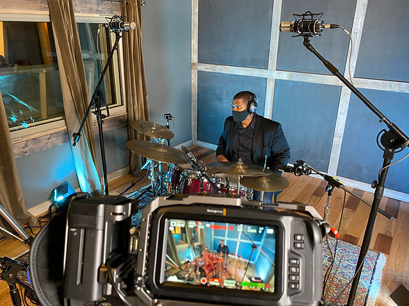 Man playing drums in studio through view of video camera recording him