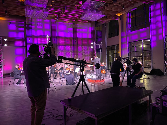 Video production scene on orchestra stage with musicianns playing classical music as video cameras record