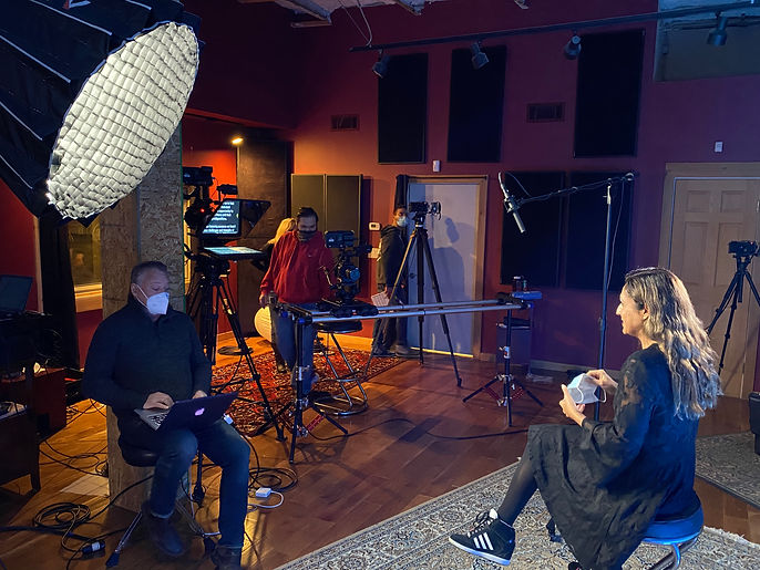 Woman sitting on bench in foreground answering questions from man with laptop and a video camera onn a dolly recording the interaction in video studio
