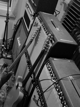 Black and white image of amps, stereos and guitars