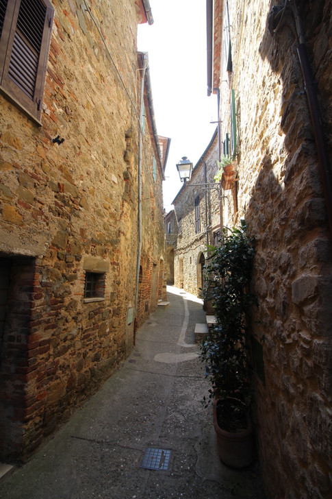 A winding street in the quaint walled village of Montemerano in Tuscany, Italy