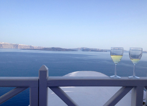 Nothing beats a glass of locally produced wine and a perfect view from our cave house in Oia, on the island of Santorini in Greece