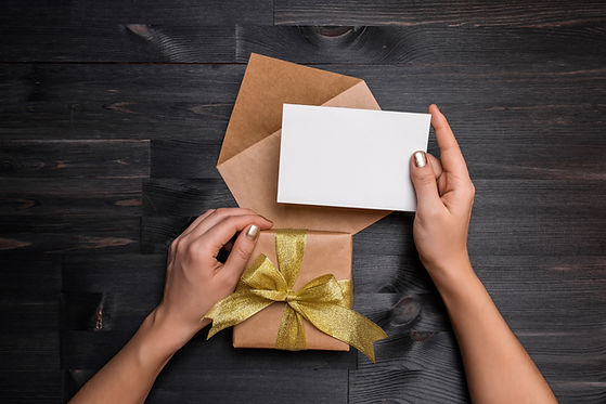 Female hands holding gift card and gift
