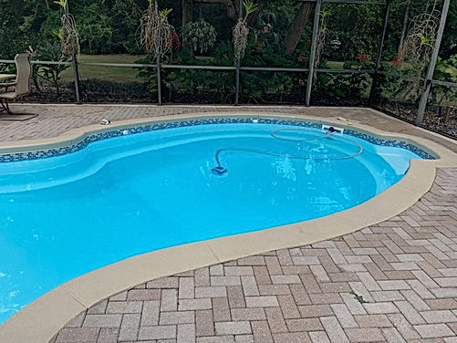 Fiberglass inground pool with tan colored pavers and a screen enclosure around the pool