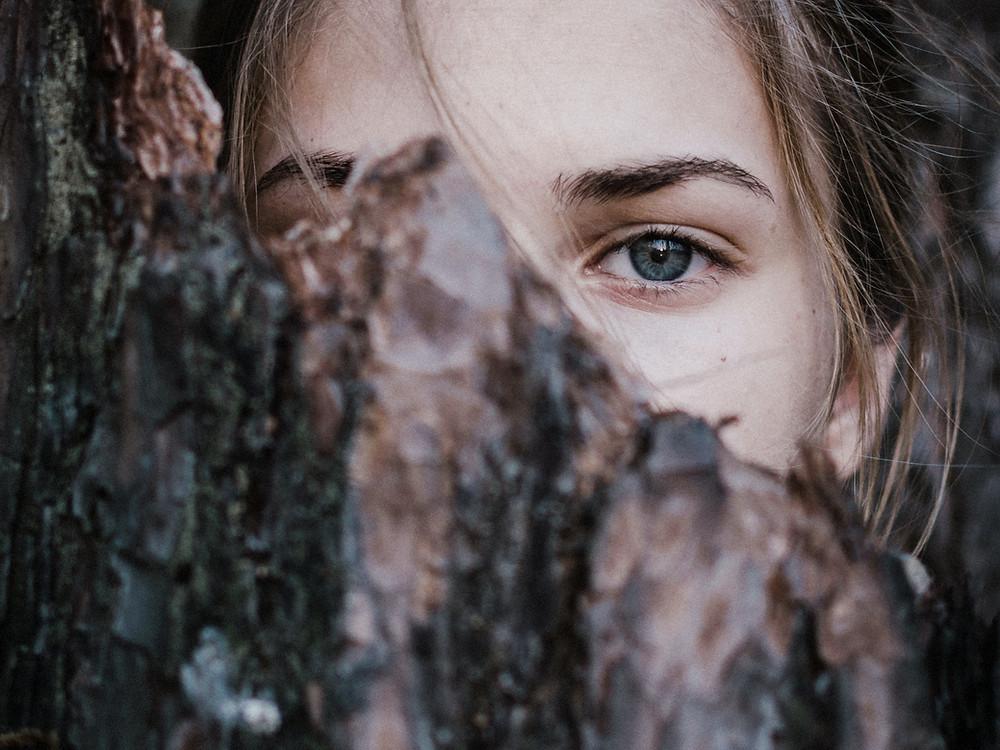 Kvinna gömmer sig bakom ett träd