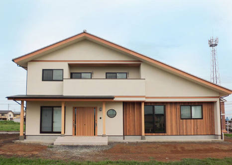 アシンメトリーな屋根と板張りの1階が印象的な家