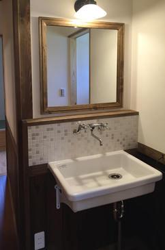 レトロな印象の洗面化粧台。 水が跳ねやすい部分にはガラスモザイクタイルを使用。
