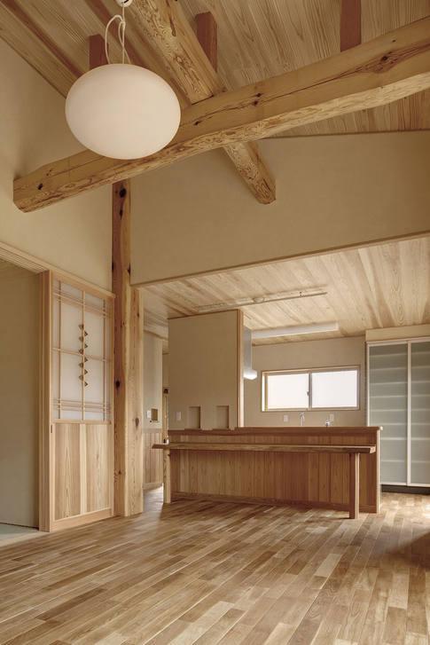 斜天井に渡る梁と、造作で作られた建具やカウンターなど使い勝手の良いLDK。