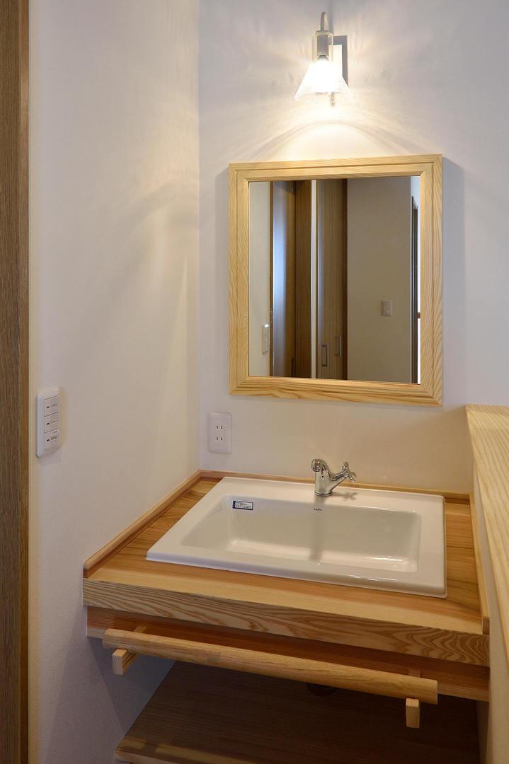 一枚板のカウンター材を使用した造作洗面台。 手前に木のバーを付けることでタオル掛けとしてお使いいただけます。