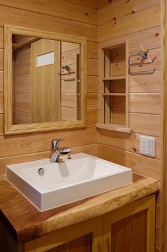 シンプルな洗面ボウルも造作棚や無垢板の壁に囲まれると、全く違った印象に。