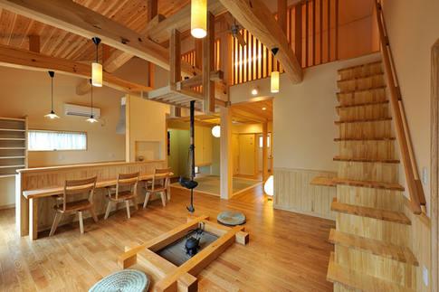昔ながらの囲炉裏のあるリビング。室内に造られた箱階段(収納+階段)を上ると、壁が格子状の小屋裏収納があります。