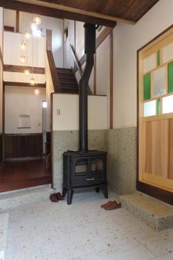吹き抜けのある玄関ホールに薪ストーブを配置し、家中暖かい。床は大谷石を使用。