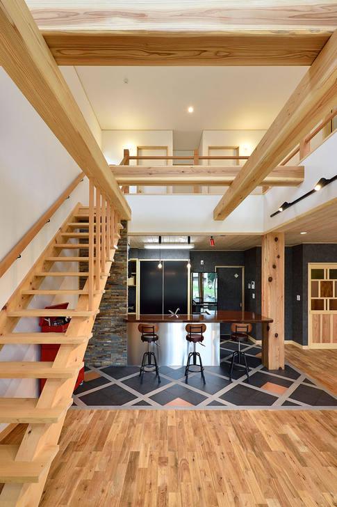 無垢材の温かみと開放的な吹き抜け、その中で異彩を放つステンレスキッチンとストーン張りの壁やタイル材が目を引くリビング。