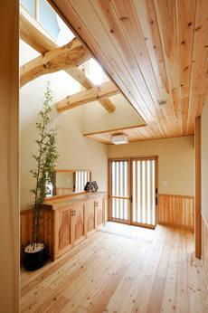 玄関の上には吹き抜けを渡る梁丸太、樹本来の美しさが楽しめる玄関。