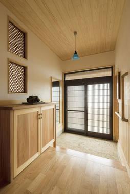 大谷石が敷き詰められた味のある玄関。お客様お持ち込みのアンティークの欄間も印象的。