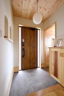 玄関ドアのサイドから光が差し込む玄関。