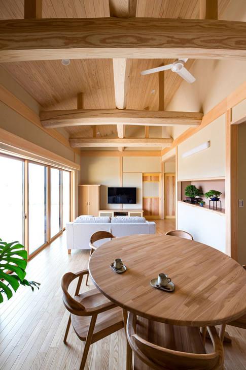 斜天井をゆったり豪快に渡る、六角落としの梁丸太が渡るリビング。ダイニング丸テーブルは造作品。