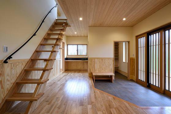 三枚引き戸の玄関戸が印象的。階段は小屋裏収納に続いています。