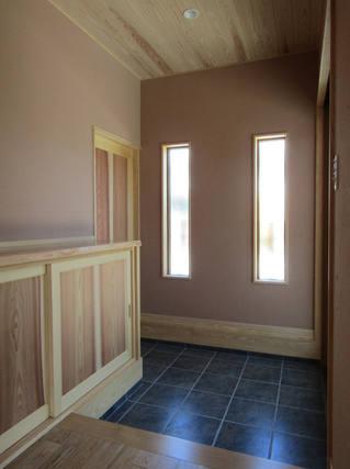 フィックス窓から差し込む光で明るい玄関。