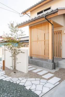 石畳のアプローチと、目隠し格子が調和した玄関