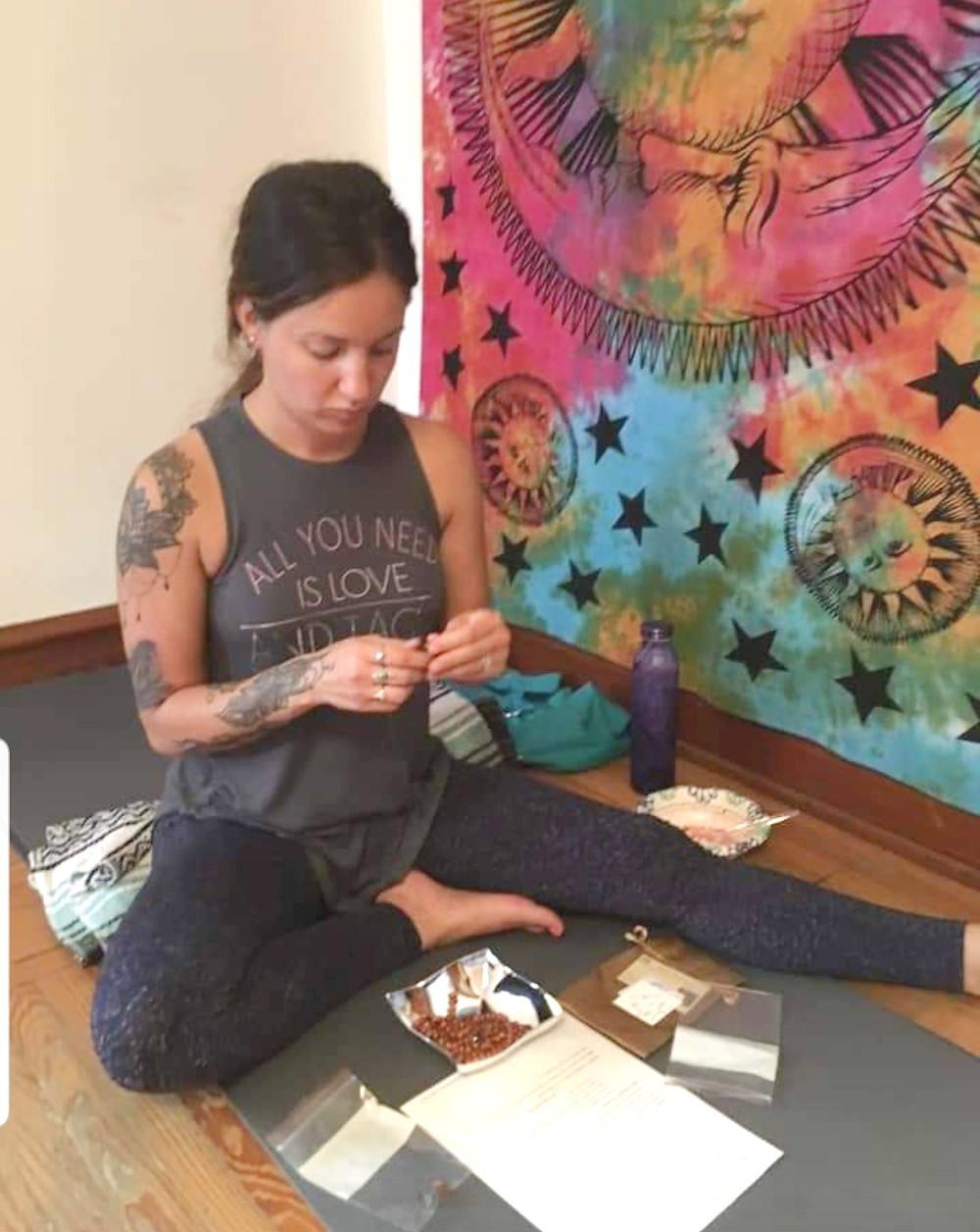 tattooed girl making jewelry, mala making process
