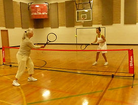 A volley rally over a portable tennis net in a gym in Calgary, Alberta