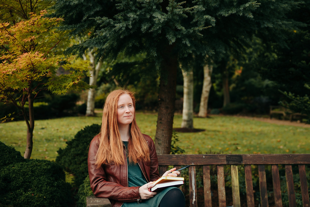 Personal branding, woman sitting on bench, thinking and writing