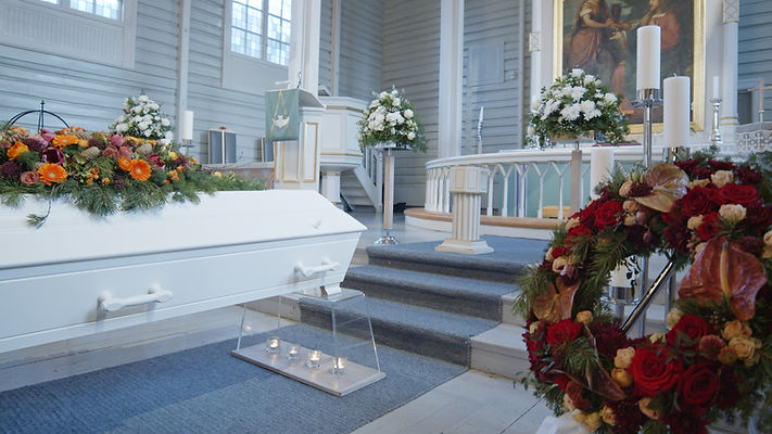 Kiste og blomster i begravelse