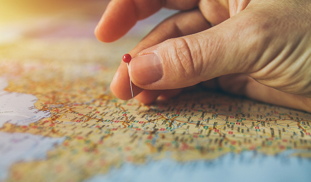 Hand pinning a location on a map
