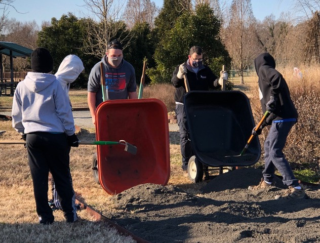 It's all hands on deck when moving tons of crushed stone from the parking lot to the garden site.