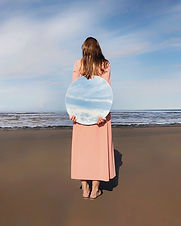 woman-standing-beside-shore-holding-mirr