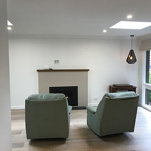 lighten the space by gyprocking over exposed dark brickwork and painting out in dulux natural white 1/2 strength; velux roof windows installed; feature gas LOPI fireplace with rustic timber mantle
