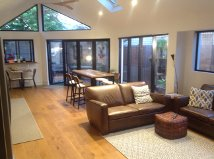kitchen/dining/lounge redesign with new Velux roof windows, modern timber ceiling fans, galley style kitchen, new bifold doors and high rise windows shaping rake of roofline